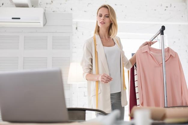 Целевая аудитория. амбициозная женщина-кутюрье смотрит на экран, держа в руках одежду