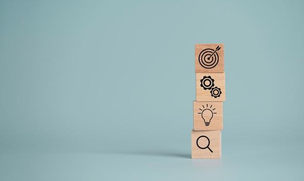 객관적인 목표와 투자 목표를 설정하기 위해 나무 큐브 블록에 화살표 인쇄 화면이있는 타겟 보드.