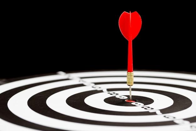 Target dart arrow hitting in the center of dartboard