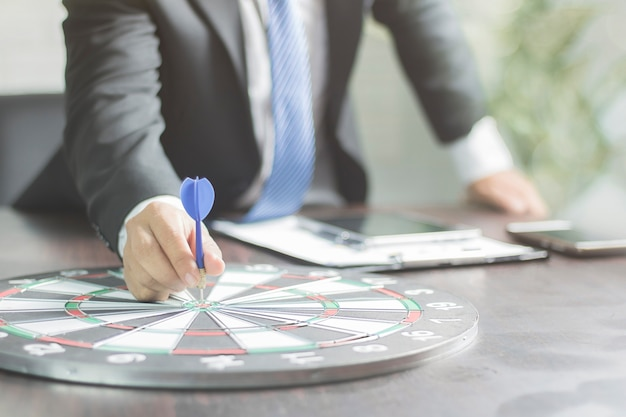 Target and goal concept, businessman attempt to get dart on board