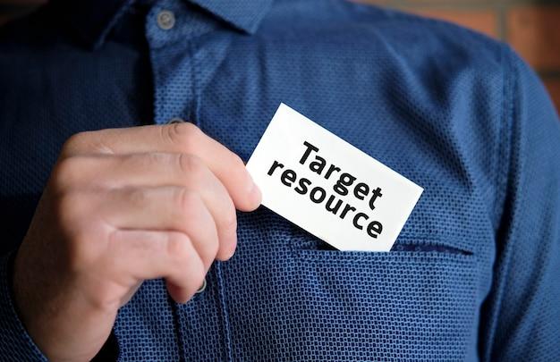 シャツを着た男の手にある白い看板のターゲットリソーステキスト