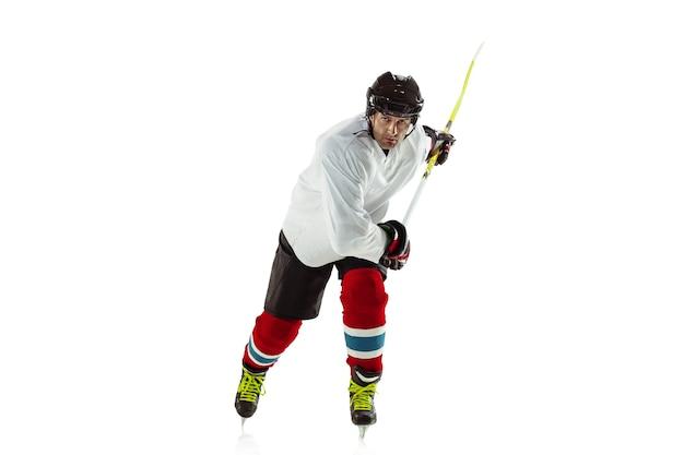 Bersaglio. giovane giocatore di hockey maschio con il bastone sul campo da ghiaccio e muro bianco. sportivo che indossa attrezzature e pratica del casco. concetto di sport, stile di vita sano, movimento, movimento, azione.