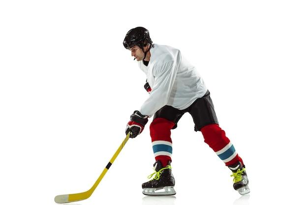 目標。アイスコートと白い壁に棒を持つ若い男性のホッケー選手。装備とヘルメットを身に着けているスポーツマンの練習。スポーツ、健康的なライフスタイル、動き、動き、行動の概念。