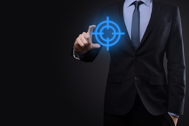Targeting concept with businessman hand holding target icon dartboard sketch on chalkboard. objective target and investment goal concept.
