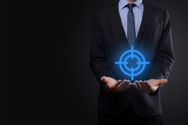 Концепция нацеливания с бизнесменом рукой, держащей целевой значок дартс на доске. объективная цель и концепция инвестиционной цели.