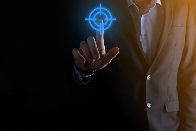 黒板にターゲットアイコンダーツボードスケッチを持っているビジネスマンの手でターゲットコンセプト。客観的な目標と投資目標の概念。