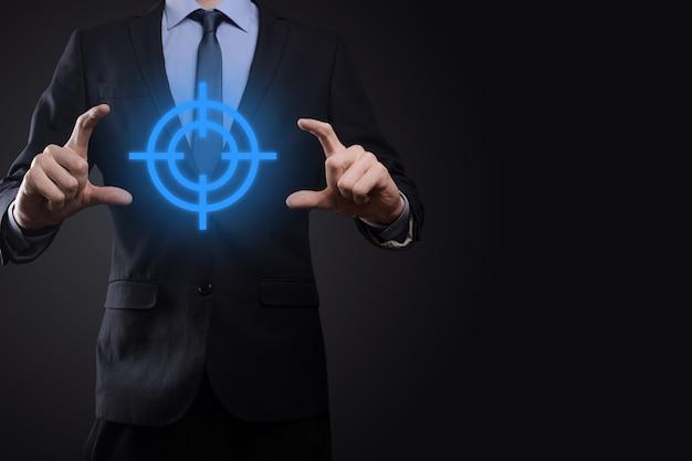 黒板にターゲットアイコンダーツボードスケッチを保持しているビジネスマンの手でターゲットコンセプト。客観的な目標と投資目標の概念。