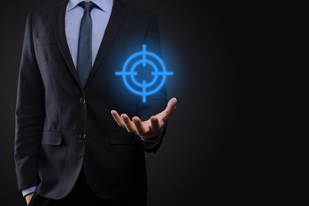 Концепция прицеливания с бизнесменом рукой, держащей целевой значок дартс на доске