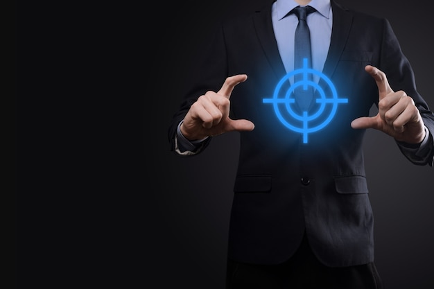 Targeting concept with businessman hand holding target symbol dartboard sketch on chalkboard. objective target and investment goal concept.