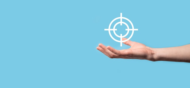 Targeting concept with hand holding target icon dartboard sketch on chalkboard.