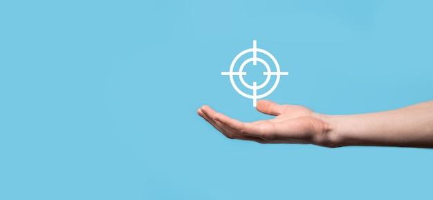 Концепция нацеливания с рукой, держащей целевой значок дартс на доске. объективная цель и концепция инвестиционной цели.