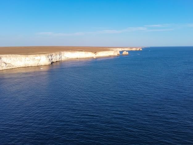 Мыс тарханкут с бирюзовой водой на западном берегу полуострова крым летний морской пейзаж известное место для путешествий живописный морской пейзаж крымский берег пляж черное море ялтинские горы