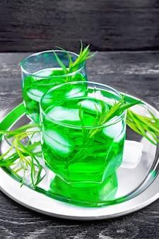 어두운 나무 판자 배경에 있는 은색 쟁반에 두 잔에 얼음을 넣은 타쿤 레모네이드