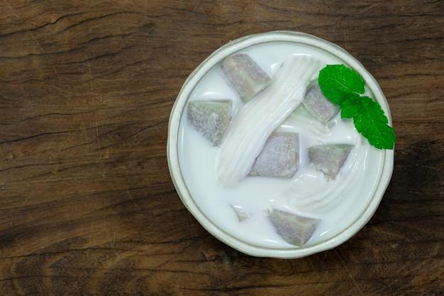 나무 배경에 흰색 그릇에 코코넛 밀크에 타로