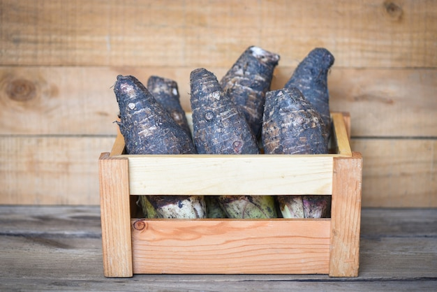 Taro root ready to cook, raw organic brown taro on wooden table