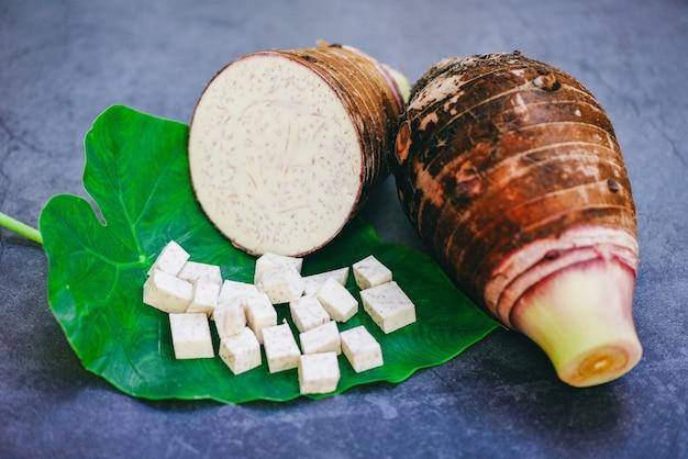 里芋の葉と木の背景に半分とスライスの立方体を持つ里芋の根、調理する準備ができて新鮮な生の有機里芋の根