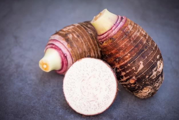 暗い背景に半分のスライスが付いた里芋、調理する準備ができている新鮮な生の有機里芋