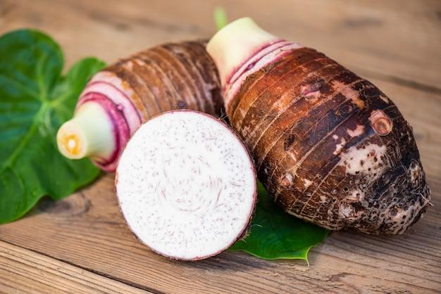 里芋の葉と木の背景に半分スライスした里芋、新鮮な生の有機里芋を調理する準備ができて