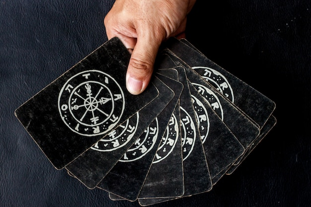 Tarot card for choosing astrological in his hand on black background
