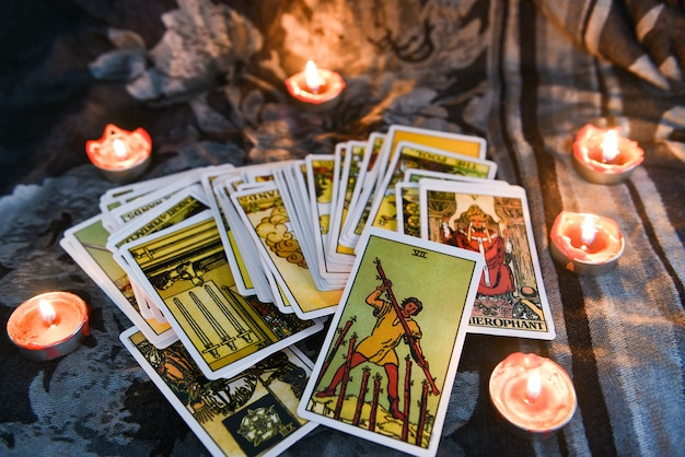 Tarot card with candlelight on the darkness background for astrology occult magic illustration - magic spiritual horoscopes and palm reading fortune teller concept