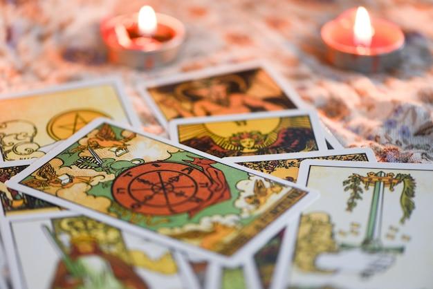 占星術オカルト魔法のイラストの暗闇の背景にろうそくの明かりが付いたタロットカード/魔法の精神占星術とパーム読書占い師