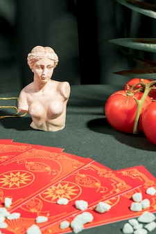 Tarot cards next to bust and tomatoes