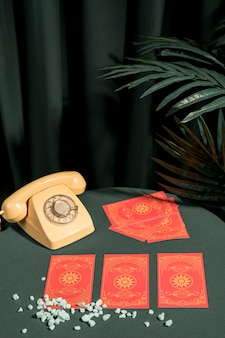 Tarot cards for good fortune next to retro phone
