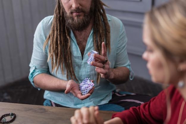 タロットカード。それらをシャッフルしながらタロットカードのパックを保持している素敵なひげを生やした男
