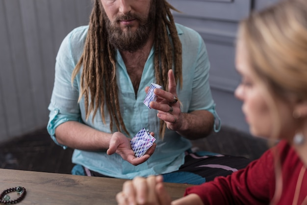 Tarot cards. nice bearded man holding a pack of tarot cards while shuffling them