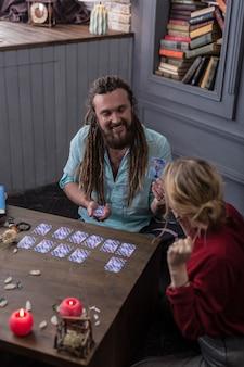 타로 카드 읽기. 그 의미에 대해 말하는 동안 타로 카드를 들고 긍정적 인 수염 난 남자의 상위 뷰