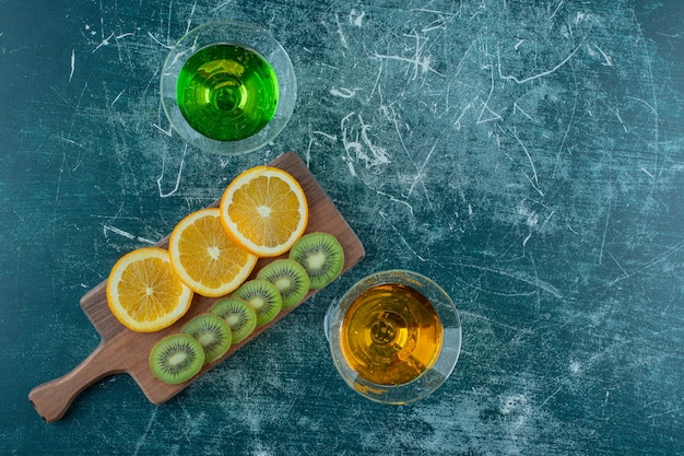 青い背景のまな板のスライスされた果物の横にあるタラゴンと梨ジュース。