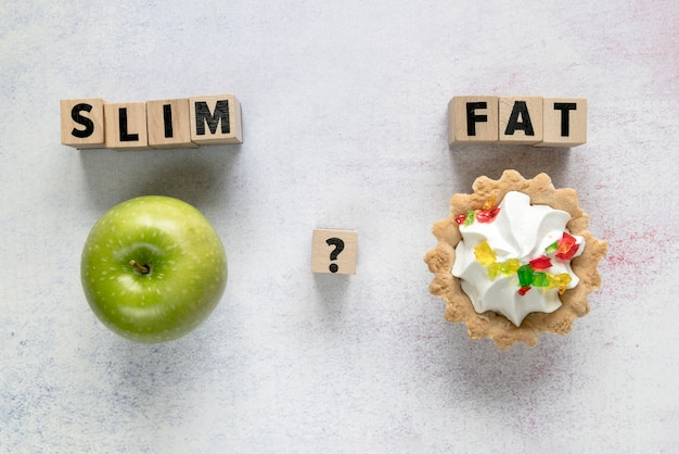 Tart cake and green apple with slim; flat text on wooden blocks over textured surface