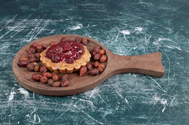 乾燥したローズヒップと木の板のタルトケーキ。高品質の写真