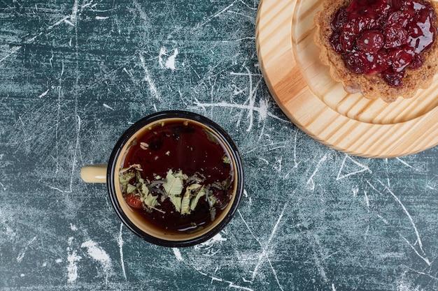 お茶と木の板のタルトケーキ。高品質の写真