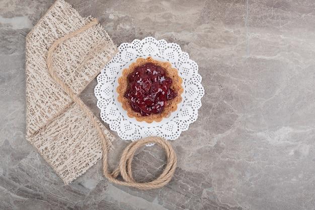 Пирог с веревкой и мешковиной на мраморной поверхности. фото высокого качества