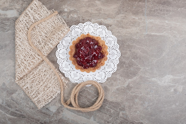 Tart cake with rope and burlap on marble surface. high quality photo