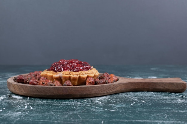 Tart cake on wooden board with dried rosehips.