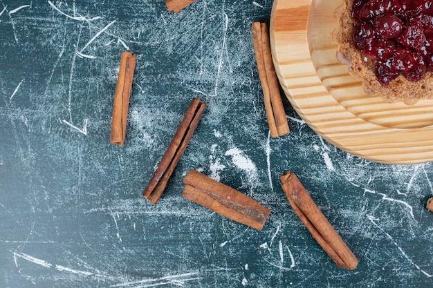Torta crostata sul piatto di legno con bastoncini di cannella. foto di alta qualità