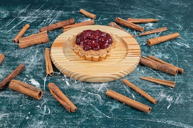 Tart cake on wooden plate with cinnamon sticks.