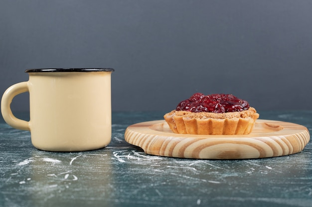 Tart cake on wooden plate with cup of tea. high quality photo