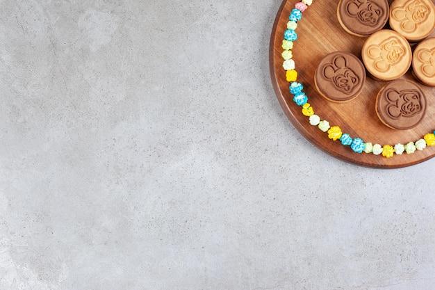 Пирог печенье, окруженный конфетами попкорна на деревянном подносе на мраморном фоне. фото высокого качества