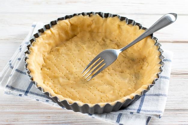Пирог (песочное тесто) в керамической форме для пирога, подготовленной для выпечки. металлическая вилка проделывает дырочки в корпусе из сырого теста