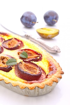 Tart of pastry with plums on a white background