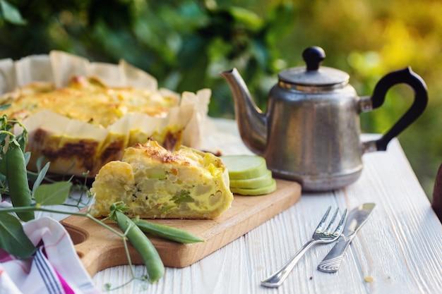 タルト。野菜のパイ-日没の光の中で庭のブロッコリー、ズッキーニ、チーズ