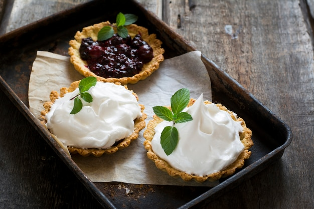 Tart with berries and icing, cream, whipped cream. open pie. valentine's day. breakfast