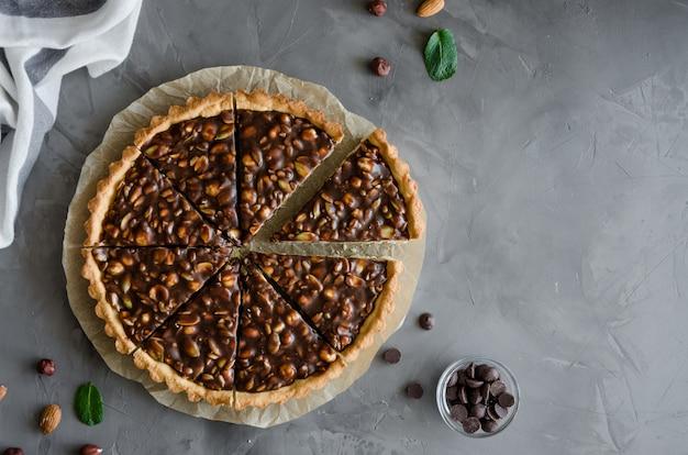 Пирог с шоколадной карамелью, фундуком, арахисом, миндалем и смесью семян на темном фоне бетона. горизонтальная ориентация. вид сверху. скопируйте пространство.