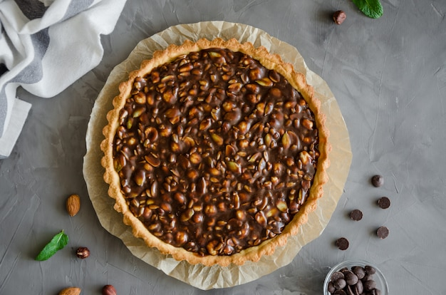 Tart with chocolate caramel, hazelnuts, peanuts, almonds and seed mix on a dark concrete background. horizontal orientation.