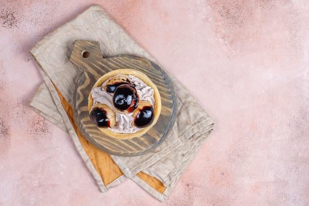 Crostata con profiteroles sopra con panna montata.