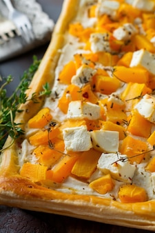 Пирог с тыквой, фетой, сыром рикотта и тимьяном на темном бетонном фоне.