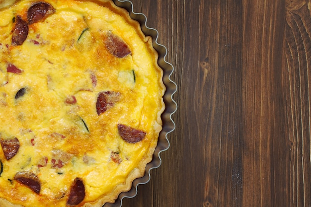 Tart with smoked sausages on brown wooden